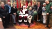 Santa Claus goes down on knees in busy shopping mall to salute a World War II veteran