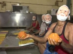 Men wearing Modi masks prepare 2,000 Kg Laddoos ahead of poll results