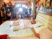In a room full of photographers, Deve Gowda strikes yogic postures on bed