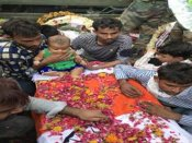 This infant sitting on her martyred father's coffin will move you to tears