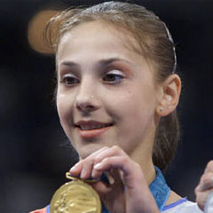 The little Raducan, a gymnast from Romania, pose with gold medal she won in all-round (individual) event in 2000 Games. However Raducan failed a drug test later and was stripped of her gold.