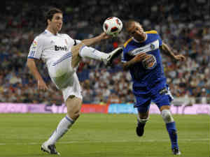 Gonzalo Higuain of Real Madrid fights for the ball with Mario Alvarez of Getafe