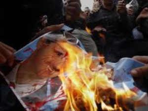 Protesters burning Syrian President Bashar al-Assad's poster