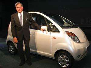 Ratan Tata posing near a Nano car
