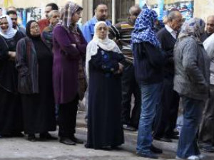 Egyptians standing out of a polling boot as the nation takes its first democratic elections