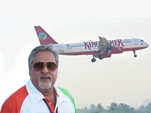 Vijay Mallya pose as a Kingfisher flight flies at the backdrop