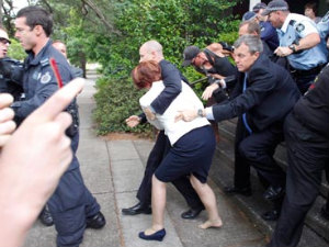 Australian PM Julia Gillard being rushed to safety by her security guards