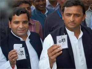 SP leaders Akhilesh Yadav and Dharmendra Yadav showing their identity cards as they wait in a queue to cast their votes during fifth phase of UP assembly polls.