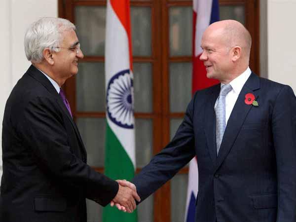 Salman Khurshid shakes and William Hague
