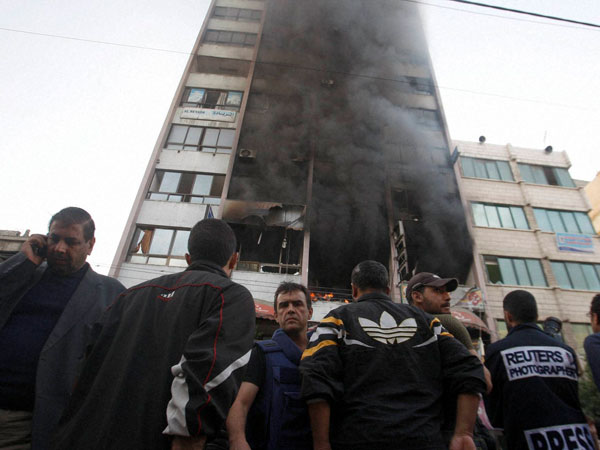 People in front of a damaged building in gaza city