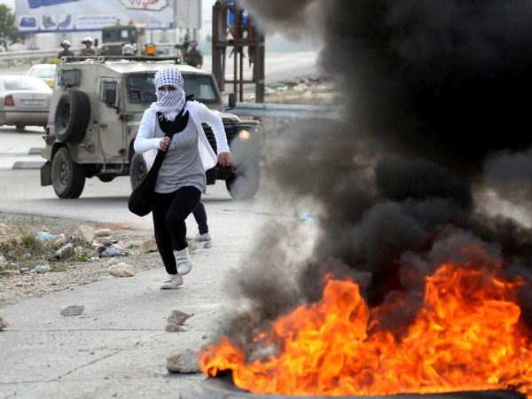 A Palestinian woman runs during clash with Israeli security forces