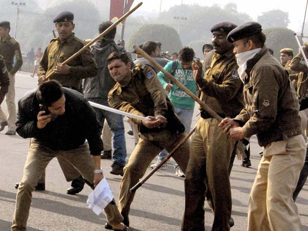 Police lathicharge a student during protest