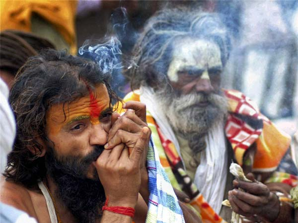 Naga sadhu smokes a chillum on a cold day