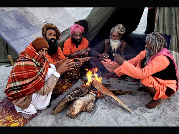 Juna Akhada Naga Sadhus warming themseleves around a fire