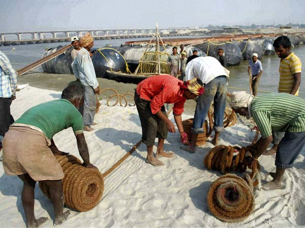 Labourers work to construct a temporary pontoon bridge