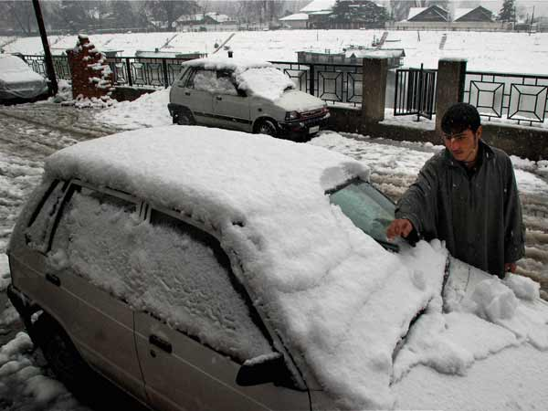 A man cleans snow from his car
