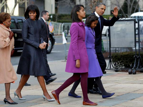 Barack Obama waves as he walks with his daughters