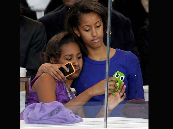 Malia and Sasha look on from the presidential box during the Inaugural parade