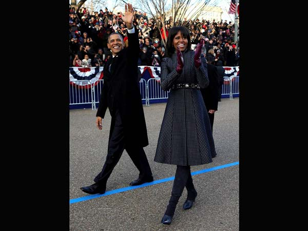 Barack Obama and Michelle Obama wave as they walk down Pennsylvania Avenue