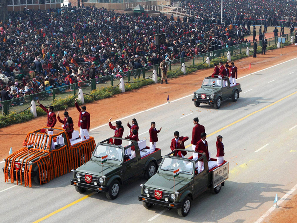 Brave children wave from open vehicles at Rajpath