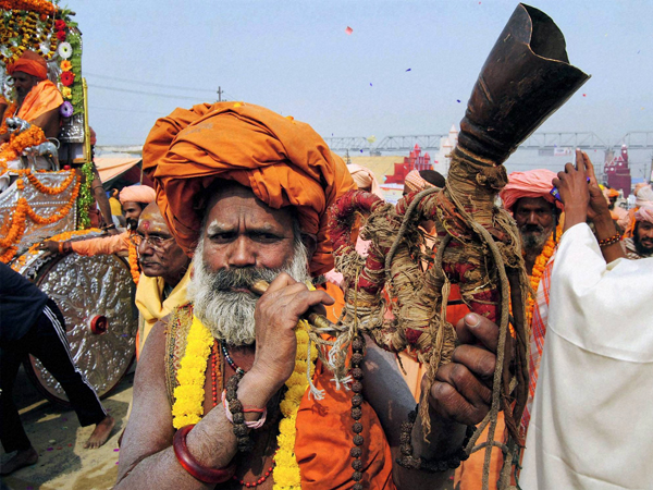 A sadhu playing a bugle