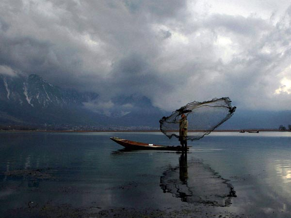 A fisherman casts his net at the Dal Lake