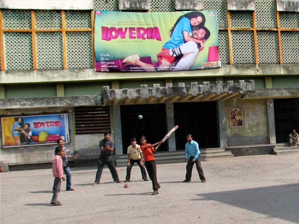 Children Play cricket in front of a closed cinema hall