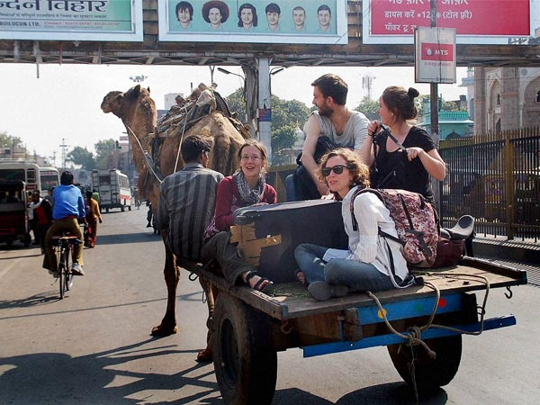 Foreign Tourists travel on a camel cart