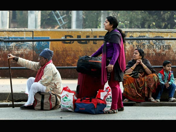 Passengers wait for Transport with their luggage