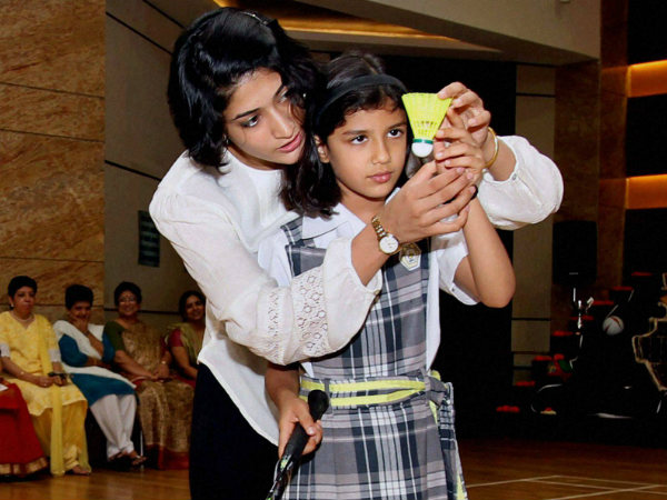 Ashwini Ponnappa giving tips to a school girl during the launch of