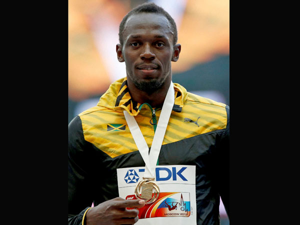 Usain Bolt shows off his gold medal