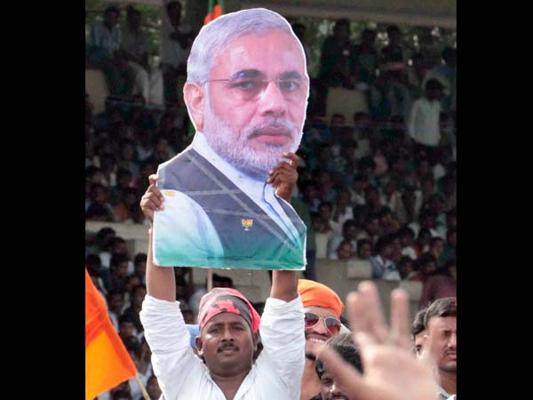 A supporter with a cut-out of Modi