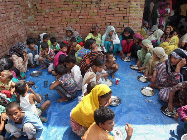 Riot-affected women and children having food