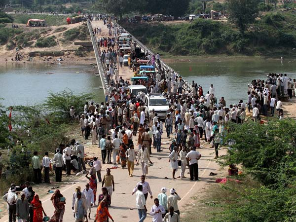 People gather near the bridge on the Sind River