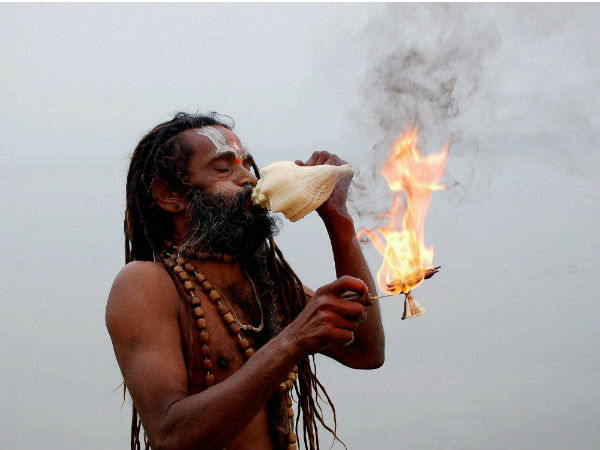 An sadhu performs arti after taking holy dip in river Ganga