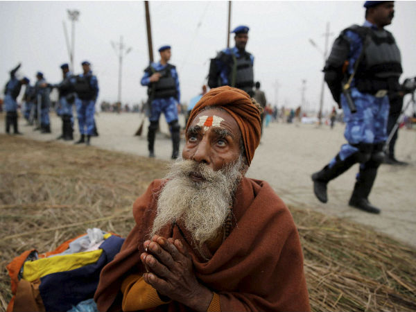 An elderly devotee prays as RAF soldiers patrol at Sangam