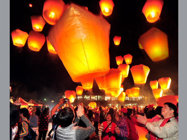 People light sky lanterns