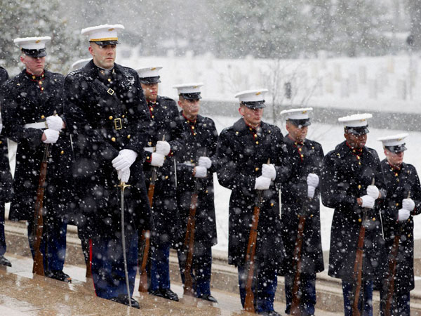 A US Marine Corps Honor Guard stand guard in the falling snow