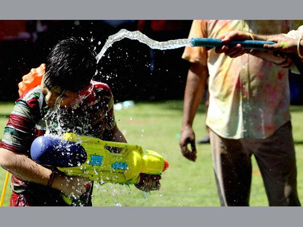 A boy play with water during Holi celebrations