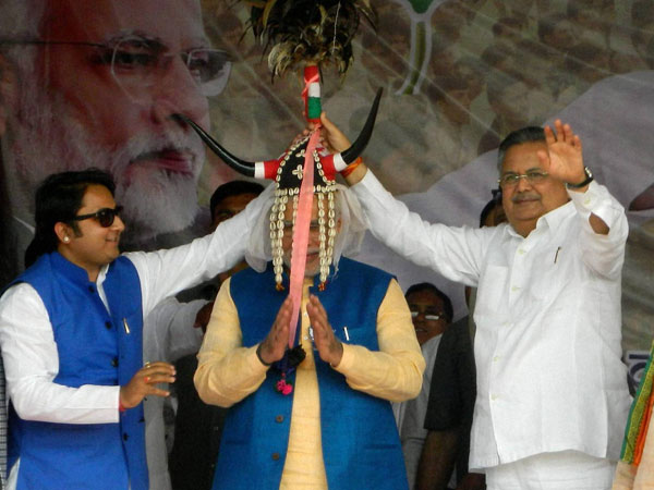 Narendra Modi wears a headgear presented by Chhattisgarh Chief Minister Raman Singh