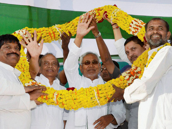 Nitish Kumar being garlanded by supporters at election meeting