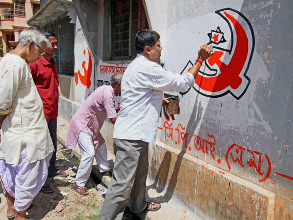 CPI(M) workers prepare party symbol on a wall
