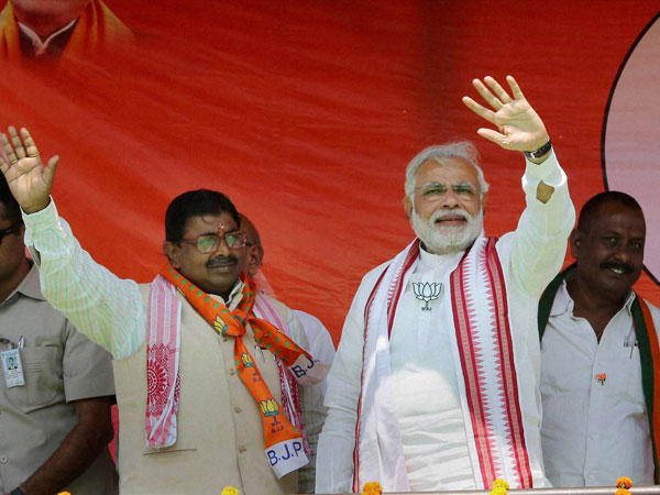 Narendra Modi waves to supporters during an election campaign