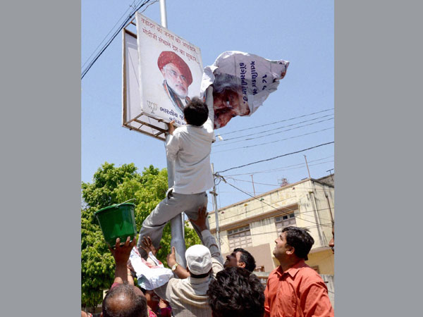 Madhunsudan Mistry pasting his poster over a poster of Narendra Modi