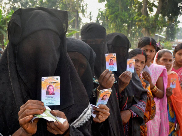 Voters show their voter ID cards outside a polling booth