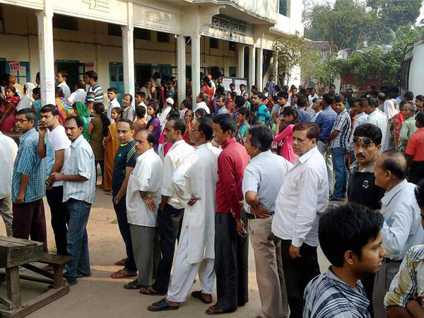 People wait in queues to cast their vote at polling booth