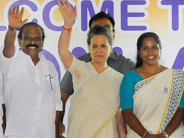 Sonia Gandhi waves to people at an election meeting in Thrissur