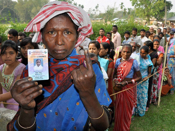 A woman shows her Voter ID card and her ink-marked finger