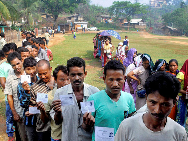 Voters queue to caste their vote in a polling station