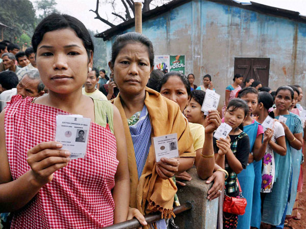 Voters stand in queue to cast their vote